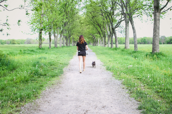 woman and dog walking down path
